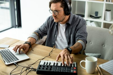 Man using laptop and audio board