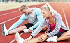 Man and woman stretching on outdoor track