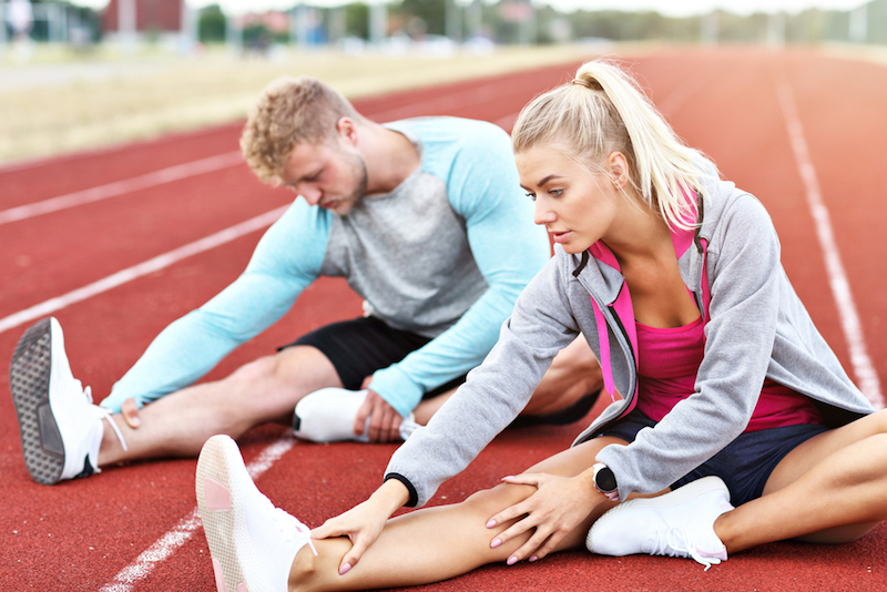 Man+and+woman+stretching+on+outdoor+track