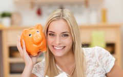 Happy young woman holding orange piggybank
