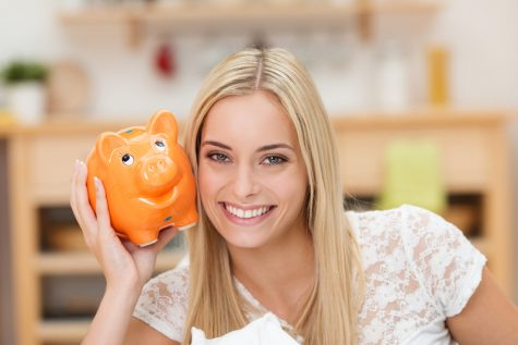 Happy young woman holding orange piggybank