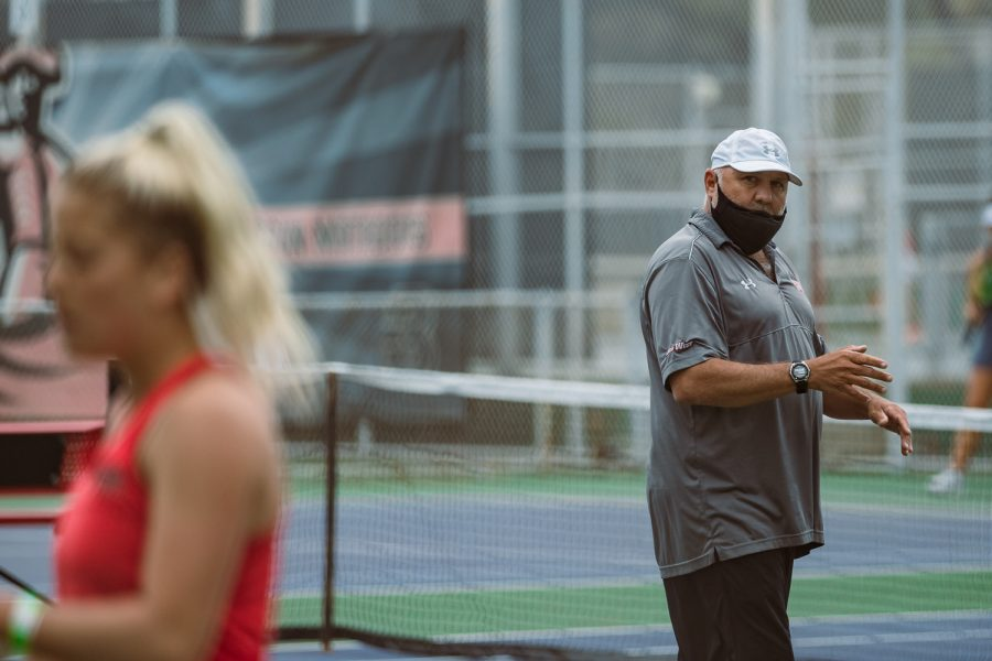 Assistant coach James Cuiffo claps his hands to encourage Jenna Dorian during her singles match at the Matador Tennis Complex in Northridge, Calif., on Wednesday, April 21, 2021.