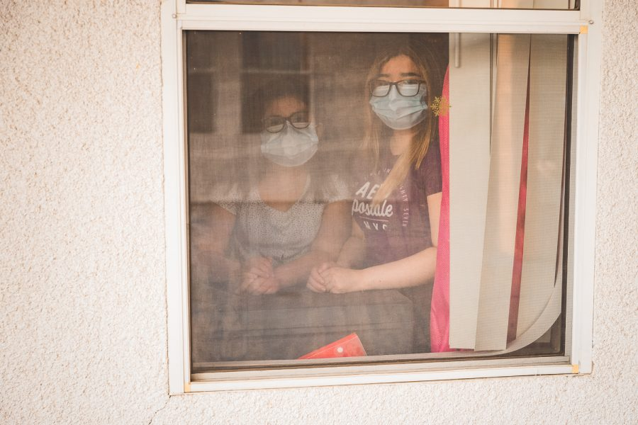 Candy, left, and Kimberly Magaña look out the window of their apartment in North Hills, Calif., on April 1, 2021.