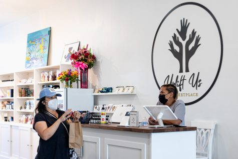 A customer chats with Kendra Settle at Uplift Us Marketplace in Granada Hills, Calif., on Saturday, Mar. 27, 2020.