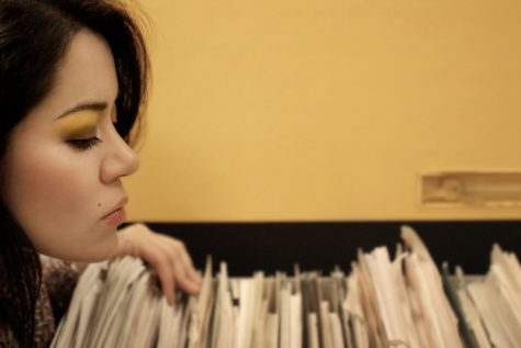 Young woman looking through papers in office