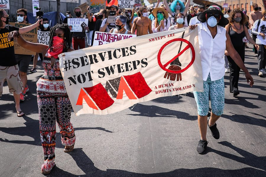 "Protesters hold up a sign advocating ""Services Not Sweeps,"" during a protest against inhumane treatment of homeless people at Venice, Calif., on July 5, 2020."