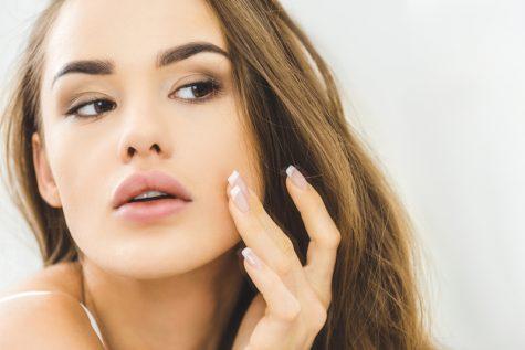 woman examining her cheek