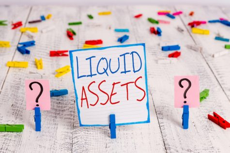 """handwritten sign saing """"Liquid Assets"""" with paper clips placed on the wooden table"""
