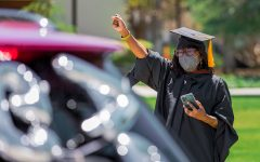 Dianah E. Wynter, a cinema and television professor, congratulates the 2020 and 2021 graduates as they drive past her during the CSUN Grad Parade at CSUN in Northridge, Calif., on Tuesday, May 25, 2021.