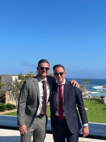 two men wearing suits and sunglasses at a seaside resort