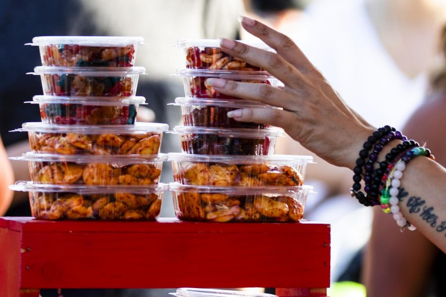 Angie Urrutia, an employee with ChiliOSO, places a fresh batch of spicy candies on a display at the 818 Night Market in Mission Hills, Calif. on July 10, 2021.