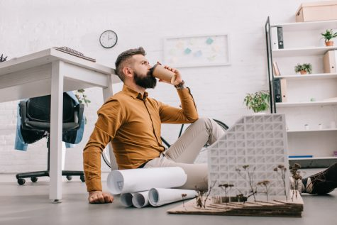 Man sitting cross-legged on floor and drinking coffee with building model by his feet