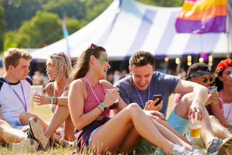Friends sitting on grass using smartphone at music festival