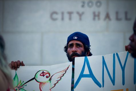 An unhoused neighbor and protester stands on the steps of Los Angeles City hall while attending a rally in opposition of a proposed motion to amend LA Municipal Code 41.18 in Downtown Los Angeles, Calif. on Wednesday, July 28 2021. As demonstrations continued LA Council Members voted in favor of the amendment, which aims to criminalize individuals who sit, lie or sleep on public property within specified times and locations; including up to 500 feet of a designated overpass, underpass, freeway ramp, tunnel or bridge.