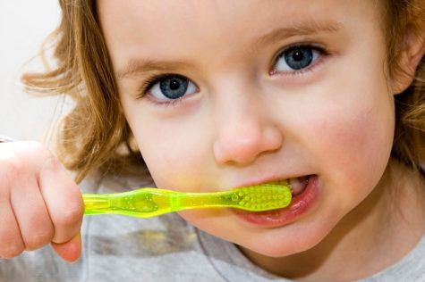 A little girl brushing her teeth against a white background.