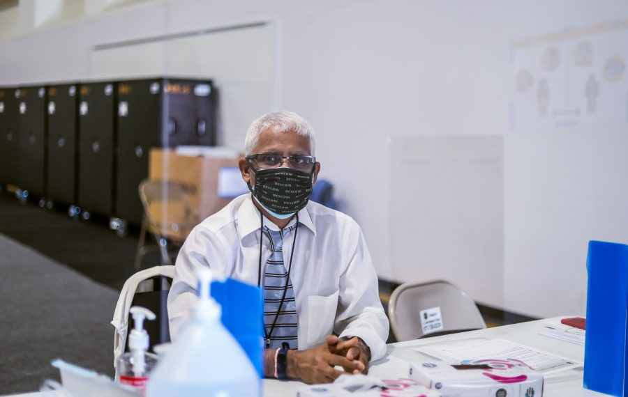 Dr. Nam Singh enforces COVID-19 safety protocols by providing hand sanitizer and reminding voters to wear their masks at the voting center in Northridge, Calif., on Tuesday, Sept. 14, 2021.