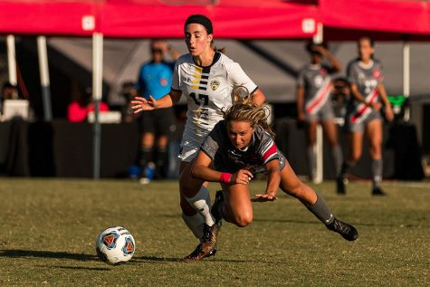 Brooke Mobeck, right, gets tripped up by a UCSD Triton defender during their match at the Performance Field in Northridge, Calif. on Wednesday, Sept. 16, 2021.