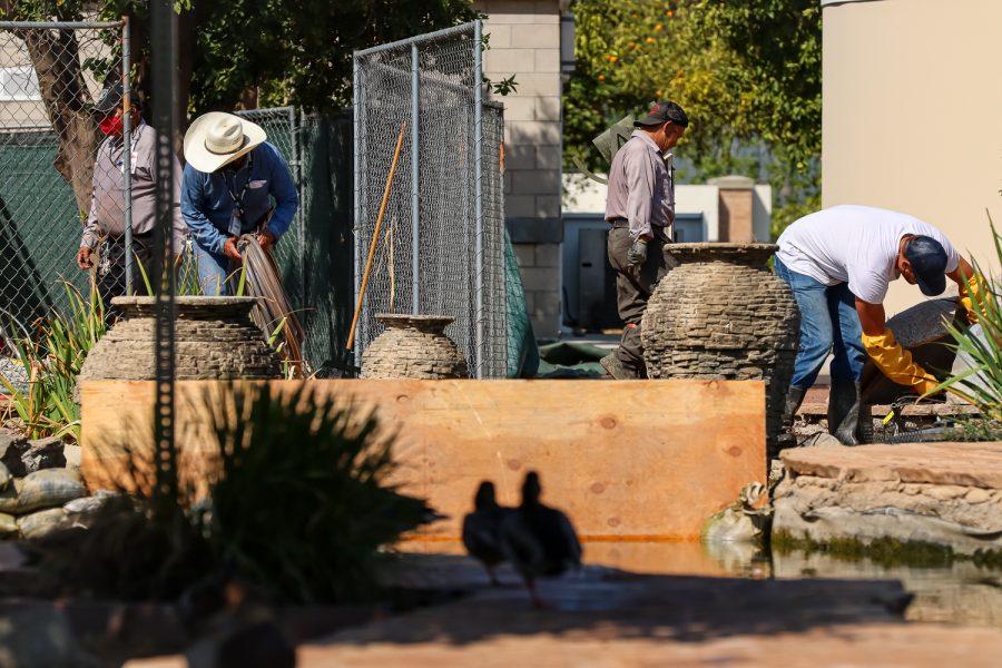 CSUN campus staff work on the pumps to the Orange Grove Pond on Sept. 6, 2021 in Northridge, Calif.