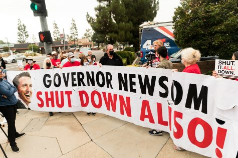 Protesters give comments to the media while holding a banner demanding Gov. Gavin Newsom to shut down the Aliso Canyon gas storage facility in Porter Ranch, Calif., on Tuesday, Sept. 28, 2021.