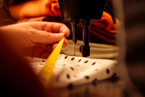 Photo illustration of hands measuring fabric on an industrial sewing machine, taken in Los Angeles, Calif. on Thursday, Oct.7, 2021.