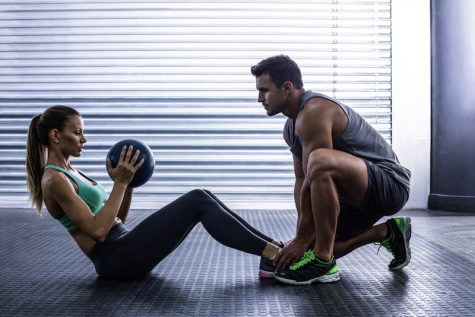 Side view of a muscular couple doing abdominal ball exercise