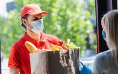 man wearing a mask delivering to groceries to mask-wearing woman