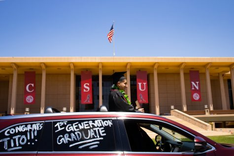 Tito, a first-generation graduate, stands through the sunroof while holding onto his diploma holder in front of the University Library during the CSUN Grad Parade in Northridge, Calif., May 25, 2021.